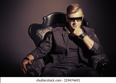 Portrait of a masculine handsome man in elegant black suit sitting in a chair in a classic vintage style.