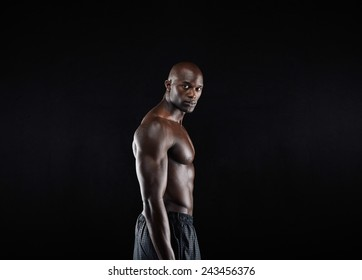 Portrait of masculine young african male model posing shirtless against black background