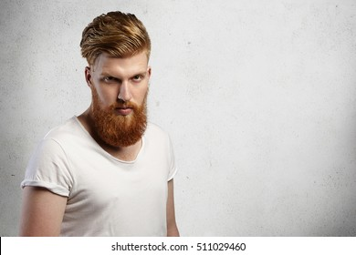 Portrait Of Masculinity. Handsome Young Bearded Hipster Man With Stylish  Haircut Looking Serious Or Angry