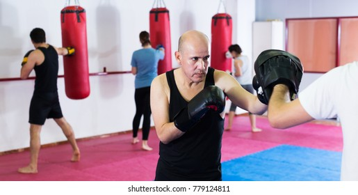 Portrait of mature active sportsmen competing in boxing gloves