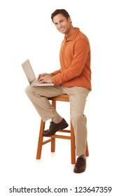 Portrait of a mature adult man wearing an orange sweater and khakis sitting on a stool working on a laptop computer looking at camera isolated on white