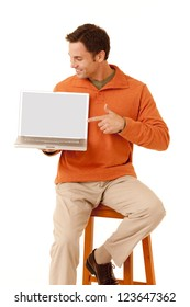 Portrait of a mature adult man wearing an orange sweater and khakis sitting on a stool pointing to the screen on a laptop computer looking at computer isolated on white isolated on white
