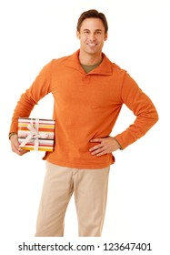 Portrait of a mature adult man wearing an orange sweater and khakis holding a gift isolated on white isolated on white