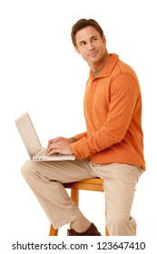 Portrait of a mature adult man wearing an orange sweater and khakis sitting on a stool displaying the screen on a laptop computer looking at camera isolated on white isolated on white