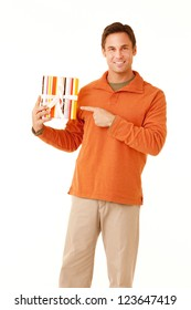 Portrait of a mature adult man wearing an orange sweater and khakis holding a wrapped gift isolated on white isolated on white