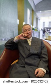 Portrait of mature Asian businessman relaxing inside the coffee shop