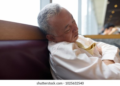 Portrait of mature Asian businessman relaxing inside the restaurant at the mall