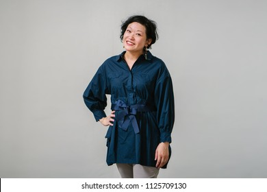 Portrait of an mature Asian Chinese woman in office wear. She is confident, attractive and smiling as she puts a hand on her hip.