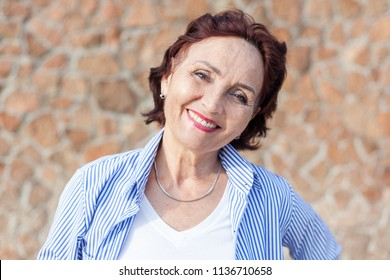 Portrait of a mature attractive  50-60 years stylish woman retired and outdoors on a summer sunny day, head shot