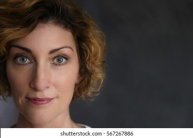 Portrait of mature attractive brunette woman with black backdrop