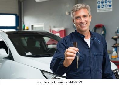 Portrait Of Mature Auto Mechanic In Garage Holding Car Key
