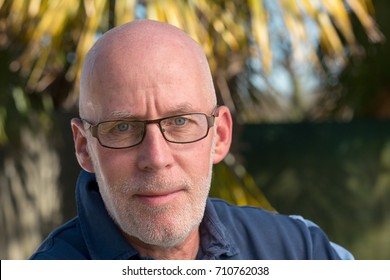 a portrait of a mature bald man with eyeglasses