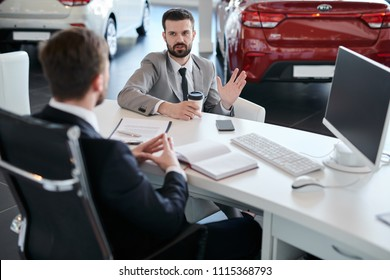 Portrait of mature bearded businessman talking to sales manager sitting across desk  in car dealership showroom, copy space