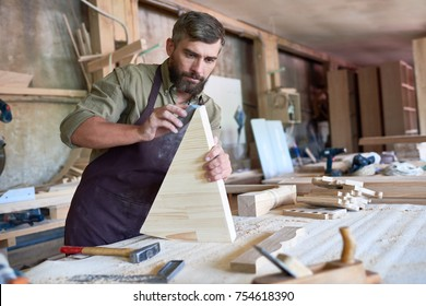 Portrait of mature bearded carpenter carefully sanding wooden part in modern workshop, copy space