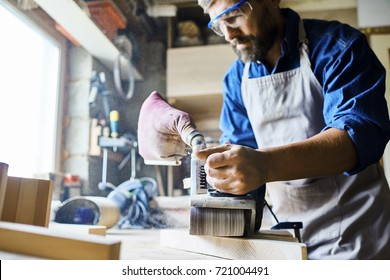 Portrait of mature bearded carpenter making furniture in workshop, polishing piece of wood standing against window in sunlight, focus on sanding machine