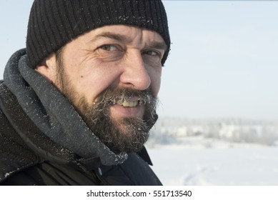 Portrait of a mature, bearded and mustachioed man in winter clothes.