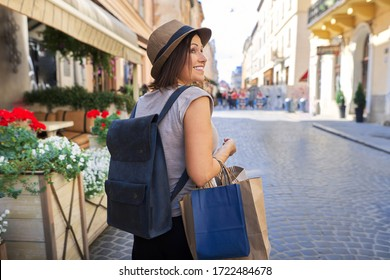 Portrait of mature beautiful successful smiling woman in hat with shopping bags, city lifestyle, urban style, copy space