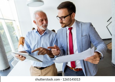 Portrait of mature boss and young business man working together in office
