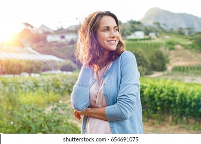 Portrait of mature brunette woman relaxing at park and looking away. Happy woman relaxing outdoor at sunset. Smiling mature woman thinking.