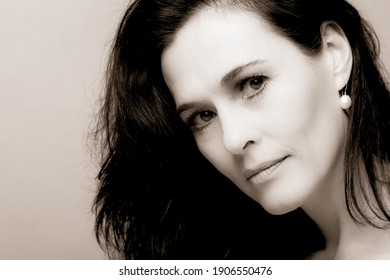 Portrait of a mature brunette woman sitting and contemplates the realities of life