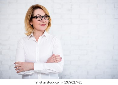 portrait of mature business woman in eyeglasses posing over white brick wall with copy space