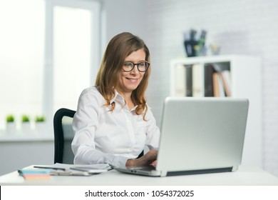portrait of a mature business woman in glasses in the office her workplace