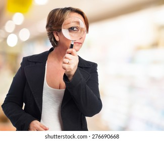 portrait of a mature business woman looking through a magnifying glass