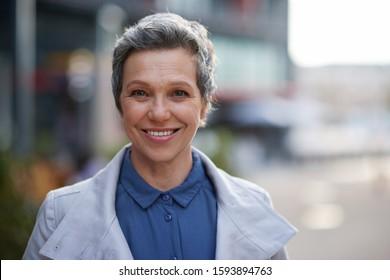 Portrait mature business woman smiling looking confident in city female success testimonial