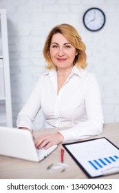 portrait of mature business woman working with laptop in modern office