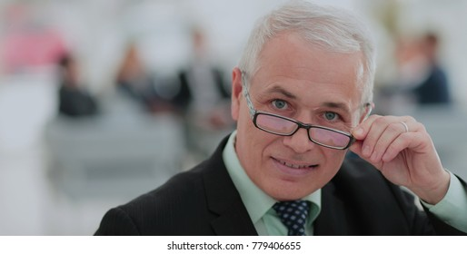 Portrait of mature businessman with  colleagues interacting on b