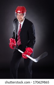 Portrait Of A Mature Businessman Dressed As Hockey Player Over Black Background