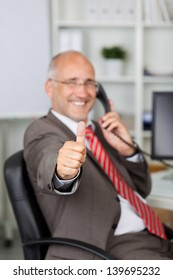Portrait of mature businessman gesturing thumbs up while using landline phone in office