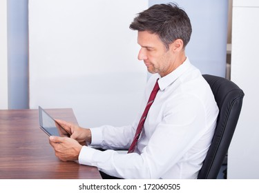 Portrait Of Mature Businessman In Office Looking At Digital Tablet