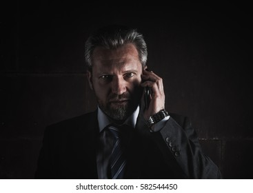 Portrait of a mature businessman on black background