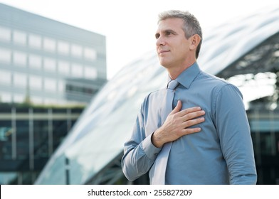 Portrait Of Mature Businessman Pledging With Hand On His Heart Outdoor