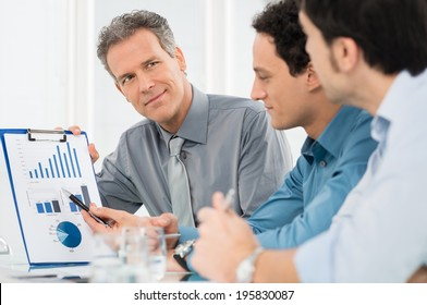 Portrait Of Mature Businessman Showing Annual Report Graph To His Colleague