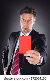 Portrait Of A Mature Businessman Showing Red Card Black Background