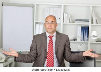Portrait of mature businessman shrugging shoulders in office