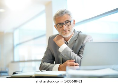 Portrait of mature businessman sitting in office looking at camera