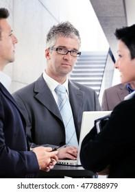 Portrait of mature businessman talking to colleagues.