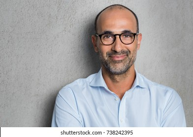 Photo of Portrait of a mature businessman wearing glasses on grey background. Happy senior latin man looking at camera isolated over grey wall with copy space. Close up face of happy successful business man.