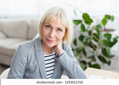Portrait of mature businesswoman looking at camera, working at home office