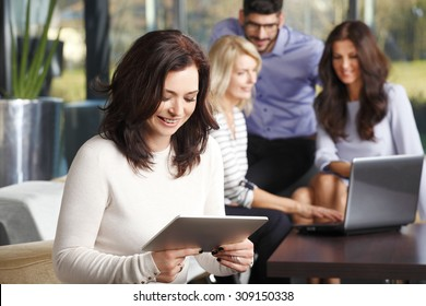 Portrait of mature businesswoman sitting at office and checking e-mails on digital tablet while her colleagues working at background in front of laptop. Teamwork at office.