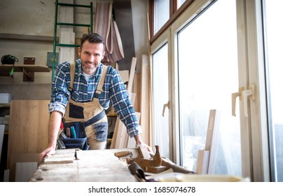 Portrait of mature carpenter posing in his carpentry workshop with tools in background