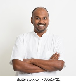 Portrait of mature casual business Indian man arms crossed and smiling, standing on plain background with shadow.