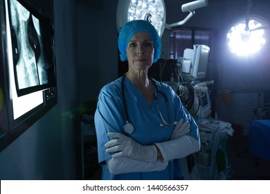 Portrait of mature Caucasian female surgeon with arms crossed looking at camera in operating room of hospital