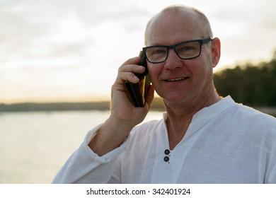 Portrait of mature Caucasian man outdoors talking on phone