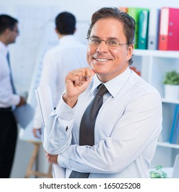 Portrait of a mature cheerful businessman posing at camera on the foreground