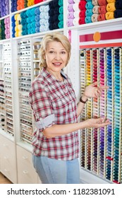 Portrait of mature cheerful female customer standing next to shelf with threads for sewing in shop