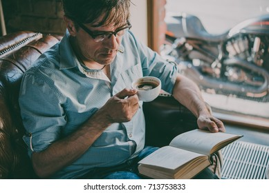 Portrait of a mature confident handsome man reading a book and enjoying his coffee. Toned picture